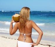 De holdingskokosnoot van de vrouw op het strand Stock Afbeelding