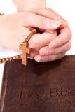 De holdingskruis van de persoon op bijbel royalty-vrije stock afbeeldingen