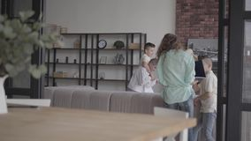 De holdingslaptop die van de portret jonge moeder door celtelefoon proberen te spreken terwijl haar vier tienerzonen die araund h stock videobeelden