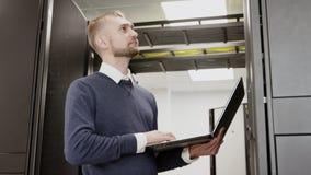 De holdingslaptop die van de systeembeheerder zich vóór serverrek bevinden stock videobeelden