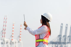 De holdingslaptop van de vrouweningenieur en het werken met de vrachtschip van de containerlading in scheepswerf bij schemer voor Stock Fotografie