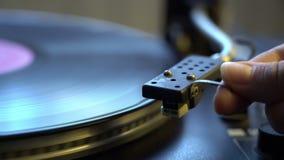 De holdingsnaald van de Cinemagraph vrouwelijke hand met naald die dichtbij vinylplaat op de oude bandrecorder spinnen stock footage