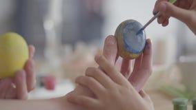 De holdingspaasei van de vrouwenhand terwijl meisje die onhandig op het een hart met een kleine dicht omhoog borstel schilderen c stock footage