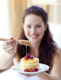 De holdingspannekoeken van de vrouw met fruit en honing Stock Foto's