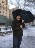 De holdingsparaplu van de Hipanicmens na lichte sneeuwdaling royalty-vrije stock fotografie