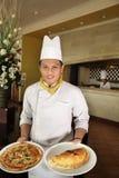 De holdingspizza van de chef-kok bij restaurant royalty-vrije stock afbeeldingen