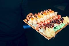De holdingsreeks van de close-upkelner van draak van de sushi de rode hebzucht, het broodjesbuffet van tonijnhokkaido Californië  stock afbeelding