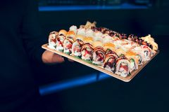 De holdingsreeks van de close-upkelner van draak van de sushi de rode hebzucht, het broodjesbuffet van tonijnhokkaido Californië  stock fotografie