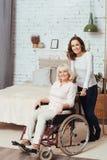 De holdingsrolstoel van de Jofulvrouw met haar grootmoeder stock afbeelding