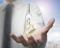 De holdingssleutel van de mensenhand met de sleutelring van de huisvorm, het 3D teruggeven Stock Afbeelding