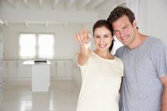De holdingssleutels van het paar in nieuw huis Stock Fotografie