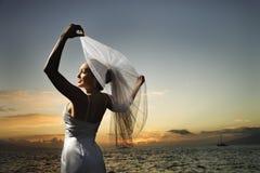 De holdingssluier van de bruid op strand Stock Foto's