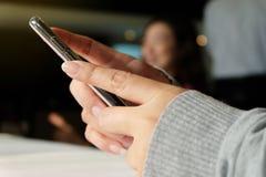 De holdingssmartphone van de vrouwen` s hand Stock Foto