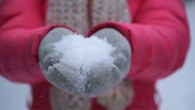 De holdingssneeuw van de lengtevrouw in handen in openlucht in de winter 4K stock video