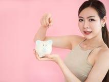 De Holdingsspaarvarken van de close-upvrouw, de besparingsgeld van het schoonheidsmeisje, Put stock fotografie