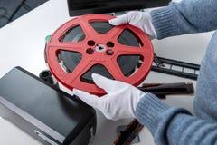 De holdingsspoel 16mm van de handenmens film Stock Afbeeldingen