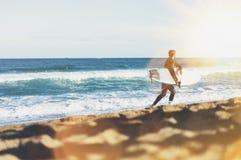 De holdingssurfplank van de surfermens op achtergrondoverzees scape, de kustlijn van het zandstrand De oceaan van de het perspect royalty-vrije stock fotografie