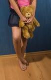 De holdingsteddybeer van het meisje tegen de muur Stock Foto's
