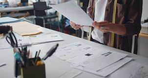 De holdingstekeningen van de klerenontwerper van kleren die in studio werken die tot kledingstukken leiden stock videobeelden