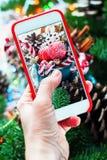 De Holdingstelefoon die van de Kerstmishand Foto schieten Stock Afbeeldingen