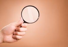 De holdingsvergrootglas van de hand op de beige achtergrond royalty-vrije stock foto