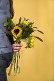 De holdingsZonnebloemen van de vrouw Royalty-vrije Stock Foto