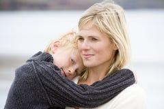 De holdingszoon van de moeder bij strand het glimlachen Royalty-vrije Stock Fotografie