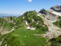 De holte tussen de bergen bij een hoogte van 2500 m De berghellingen zijn behandeld met sneeuw in de zomer stock foto