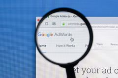 De homepagewebsite van Google Adwords op het de monitorscherm van Apple iMac onder een vergrootglas Google AdWords adverteert onl stock afbeelding