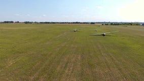 De hommel die drie zweefvliegtuigenvliegtuig op de vleugel op gebied schieten een zonnige dag stock videobeelden