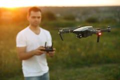 De hommel hangt voor de mens met ver controlemechanisme in zijn handen Quadcopter vliegt dichtbij proef Kerel die luchtfoto's nem stock afbeelding