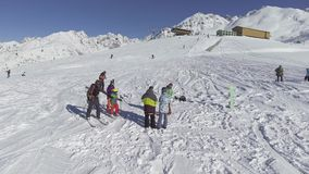 De hommel vliegt cirkels over skiërs en snowboarders op bovenkant van de de winter de sneeuw behandelde heuvel stock footage