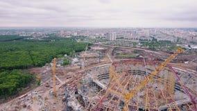 De hommel vliegt over groot bouwgebied van stadion en toont modern stadspanorama stock video
