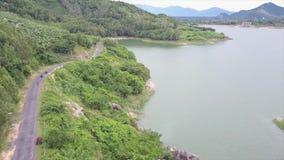 De hommel vliegt over de Weg dichtbij het meer en de berg waarop Rennende Bestuurder Driving Sporten Atv stock videobeelden