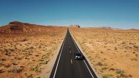 De hommel volgt twee auto's het drijven langs mooie de Monumentenvallei van de wegweg, wijd open eindeloos droog woestijnlandscha stock video