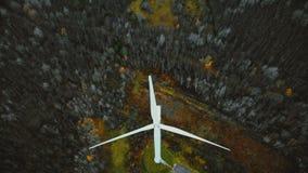 De hommelbewegingen achteruit, helt omhoog het openbaren van windmolenturbine die in de winterbos werken over, duurzame energie t stock footage