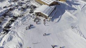 De hommelcamera toont het sneeuw behandelde hoogtepunt van de skitoevlucht van auto's en mensen op zonnige dag stock video