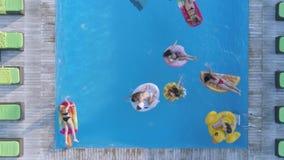 De hommelmening over bedrijf van gelukkige vrouwelijke vrienden in zwempak zwemt op Opblaasbare ringen en matras bij pool in duur stock video