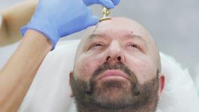 De homosexueel maakt botox injectie in voorhoofd in schoonheidskliniek stock video