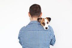 De hond ligt op de schouder van zijn eigenaar Jack Russell Terrier in de handen van zijn eigenaar op witte achtergrond Het concep royalty-vrije stock afbeelding