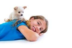 De hond van puppychihuahua bij jong geitjemeisje het liggende gelukkige glimlachen Stock Fotografie
