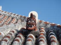 De hondbeschermer van de Shisaleeuw op een traditioneel tegeldak in Okinawa, Japan Stock Foto's