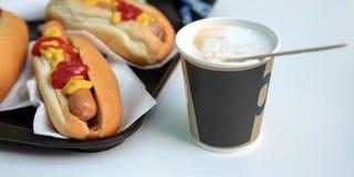 De-honden, saus, ketchup, koffie met melk in een Kop latte stock afbeelding