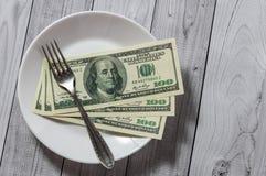 De honderd dollarsrekeningen liggen in een plaat met een vork op een lichte houten achtergrond royalty-vrije stock foto's