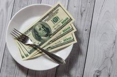 De honderd dollarsrekeningen liggen in een plaat met een vork op een lichte houten achtergrond royalty-vrije stock afbeelding