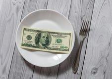 De honderd dollarsrekeningen liggen in een plaat met een vork op een lichte houten achtergrond stock afbeelding