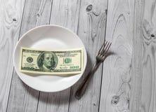De honderd dollarsrekeningen liggen in een plaat met een vork op een lichte houten achtergrond royalty-vrije stock foto