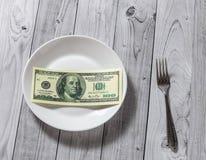 De honderd dollarsrekeningen liggen in een plaat met een vork op een lichte houten achtergrond royalty-vrije stock fotografie