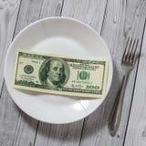 De honderd dollarsrekeningen liggen in een plaat met een vork op een lichte houten achtergrond royalty-vrije stock afbeeldingen