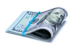 De honderd dollarsrekeningen worden gebogen in de helft met elastiekje Stock Foto